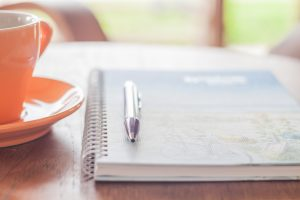 Coffee Cup With Pen And Spiral Notebook