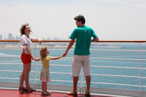 Family With Daughter Standing On Cruise Liner Deck And Holding F